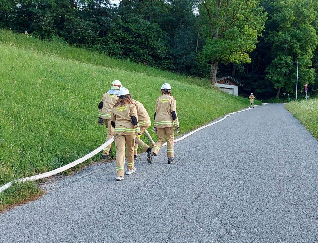Personen die Feuerwehrschläuche verlegen