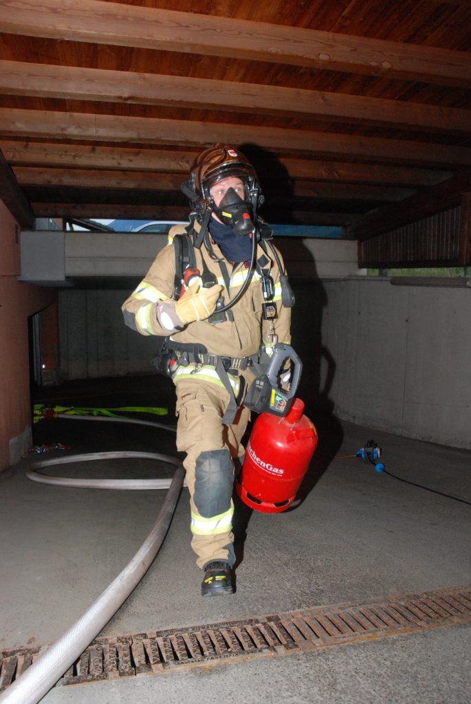 Atemschutzträger bringt Gasflasche aus dem Brandobjekt